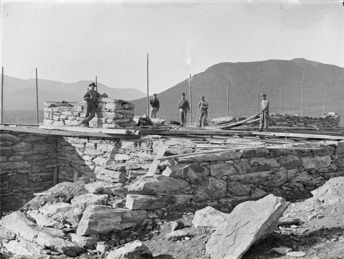 Hjerkinn gård på Dovrefjell. Fjøset under bygging. Fem arbeidsfolk.
