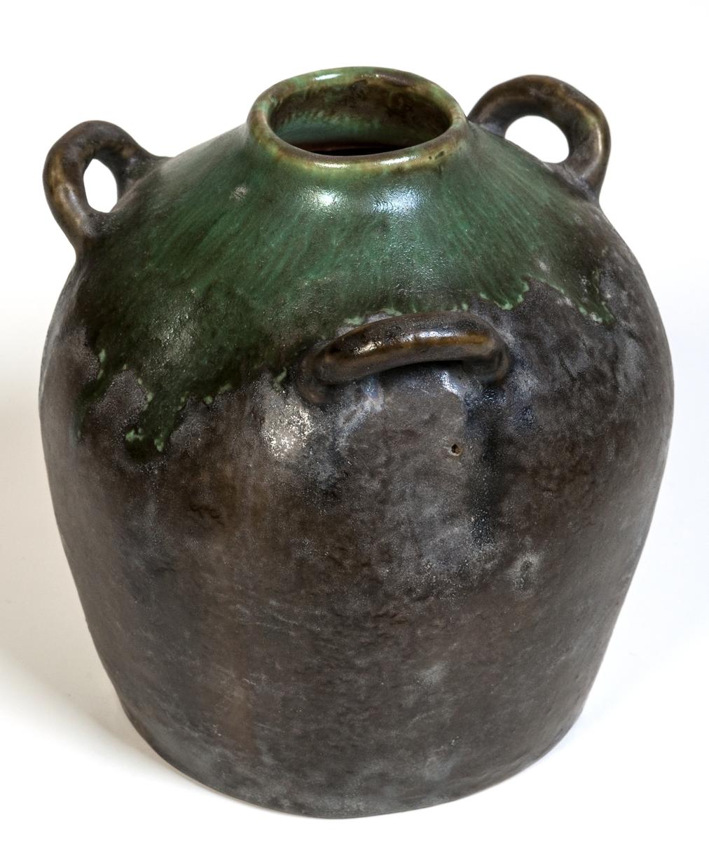 Vas med tre hänklar, höjd 11 cm, grön och gråbrun metallglasyr. Formgivare Gösta Boberg, Bobergs Fajansfabrik, Gävle.