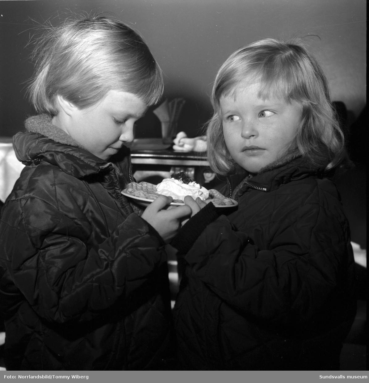 Inför våffeldagen poserar en kvinna och två barn med en våffla med sylt och grädde på ett fat.