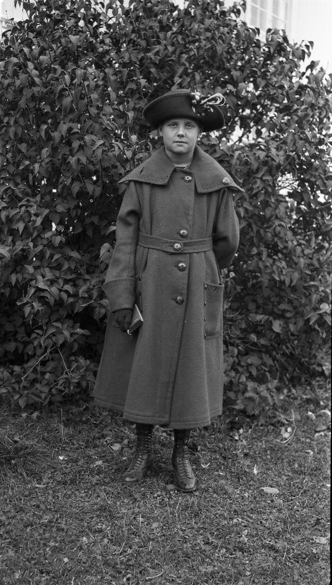 To portretter av Asta Lovise Gunnerød i helfigur. Bildene er trolig tatt i forbindelse med hennes konfirmasjon i oktober 1920. Boka hun holder i hånda på det første bildet har påtrykt en dato som kan tydes dithen.