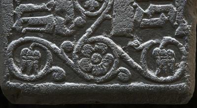 Detalj fra en middelaldergravstein; en flott uthugget fembladet blomst med bladranker rundt. (Foto/Photo)