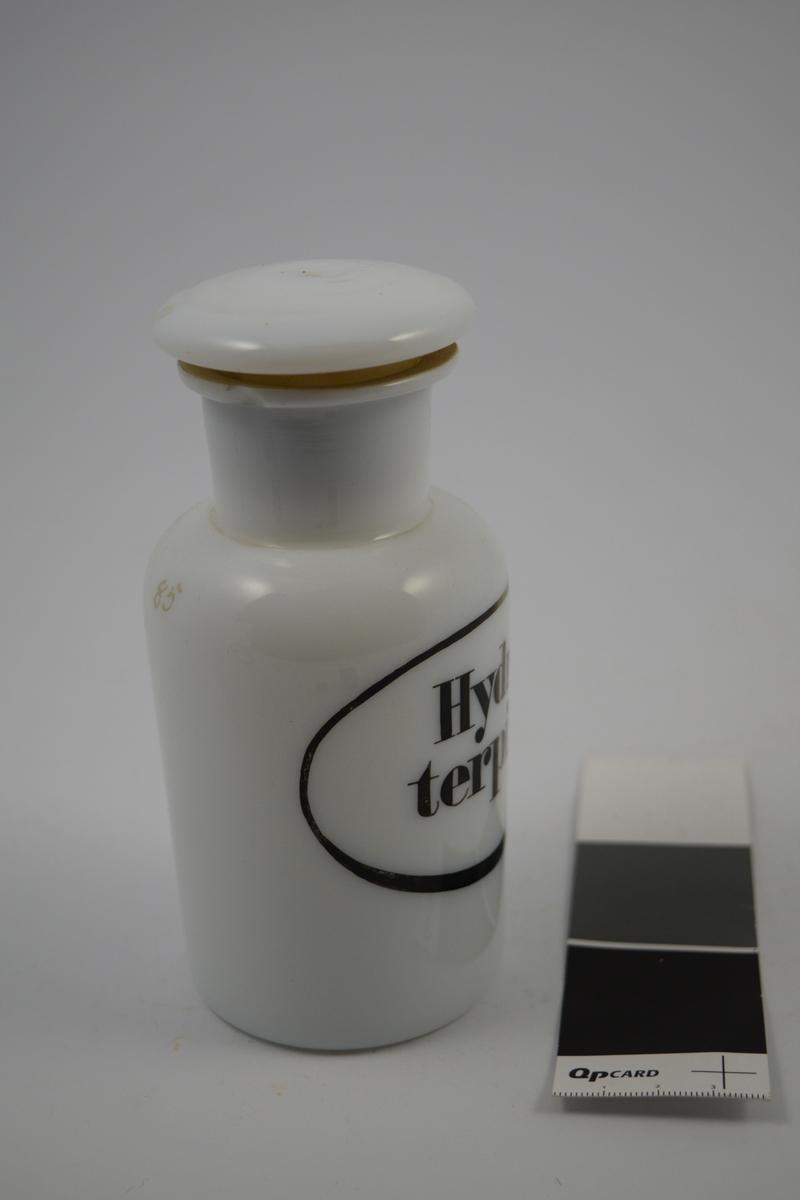 Porselenskrukke med propp. Sort oval etikett påført på krukken. Til oppbevaring av legemidler/pulver.