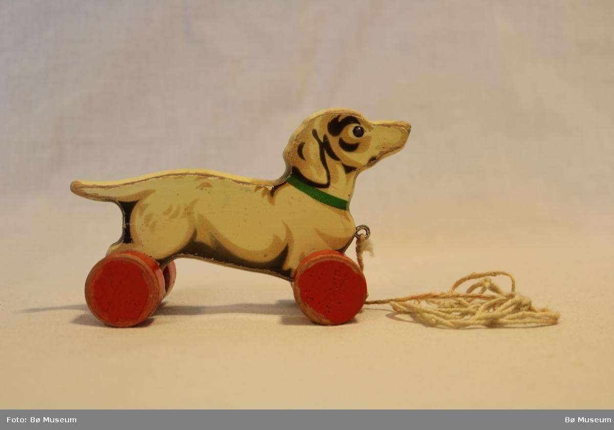 Utskore og måla figur. Forma som ein hund og og med fire hjul. Under hovudet står ein krok som det er festa hyssing til. Målinga er avflassa nokre stader.