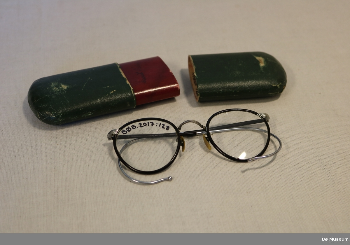 Eit par briller med tilhørande etui. Brillene har runde glas og bøyde stenger til å feste bak øyret.