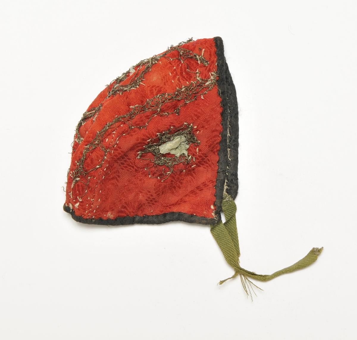 Dåpslue i raud ullbrokade pynta med sølv-kiplingar og roser av silkeband. Luva er kanta med svart brokade stoff og har grønne ripsband.  Fòra med ubleikt lin.