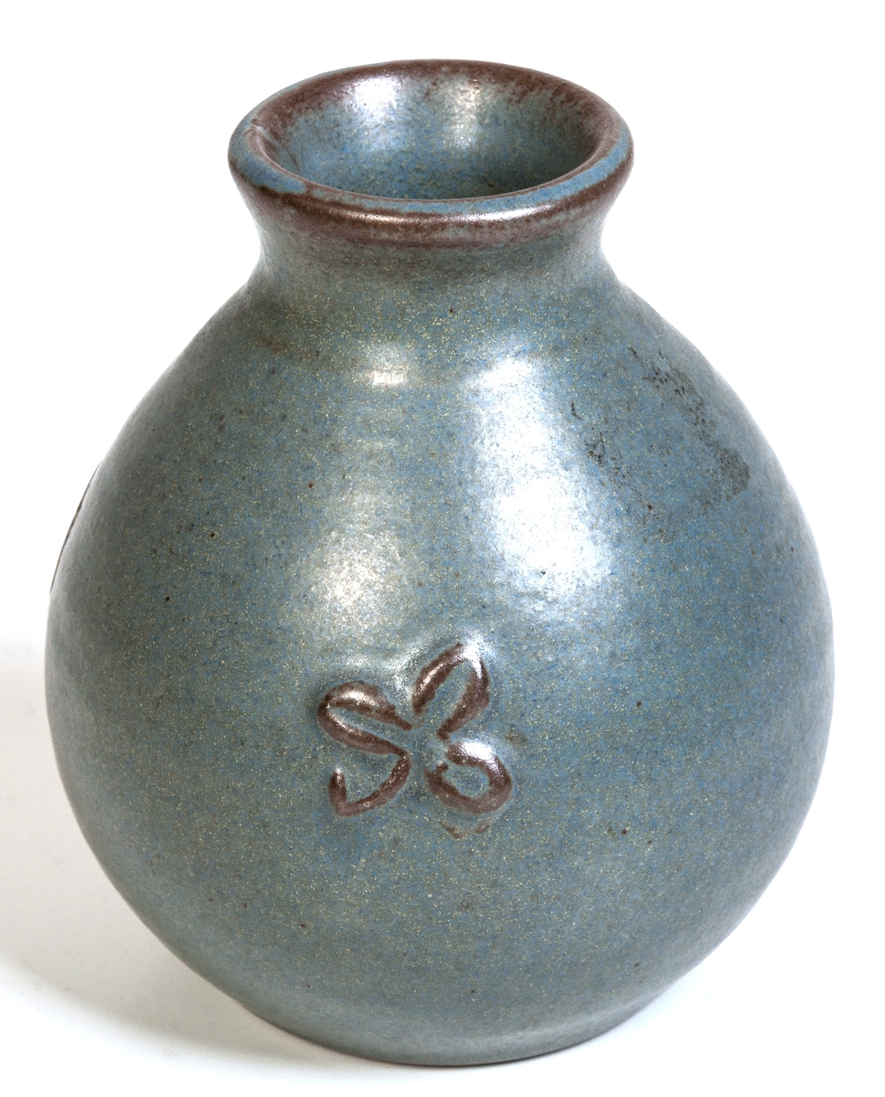 Liten vas av lergods tillverkad vid Bobergs Fajansfabrik i Gävle. Grön glasyr med två små bladreliefer. Kan vara formgiven av Maggie Wibom eller Eva Jancke-Björk. Oklar märkning i botten.