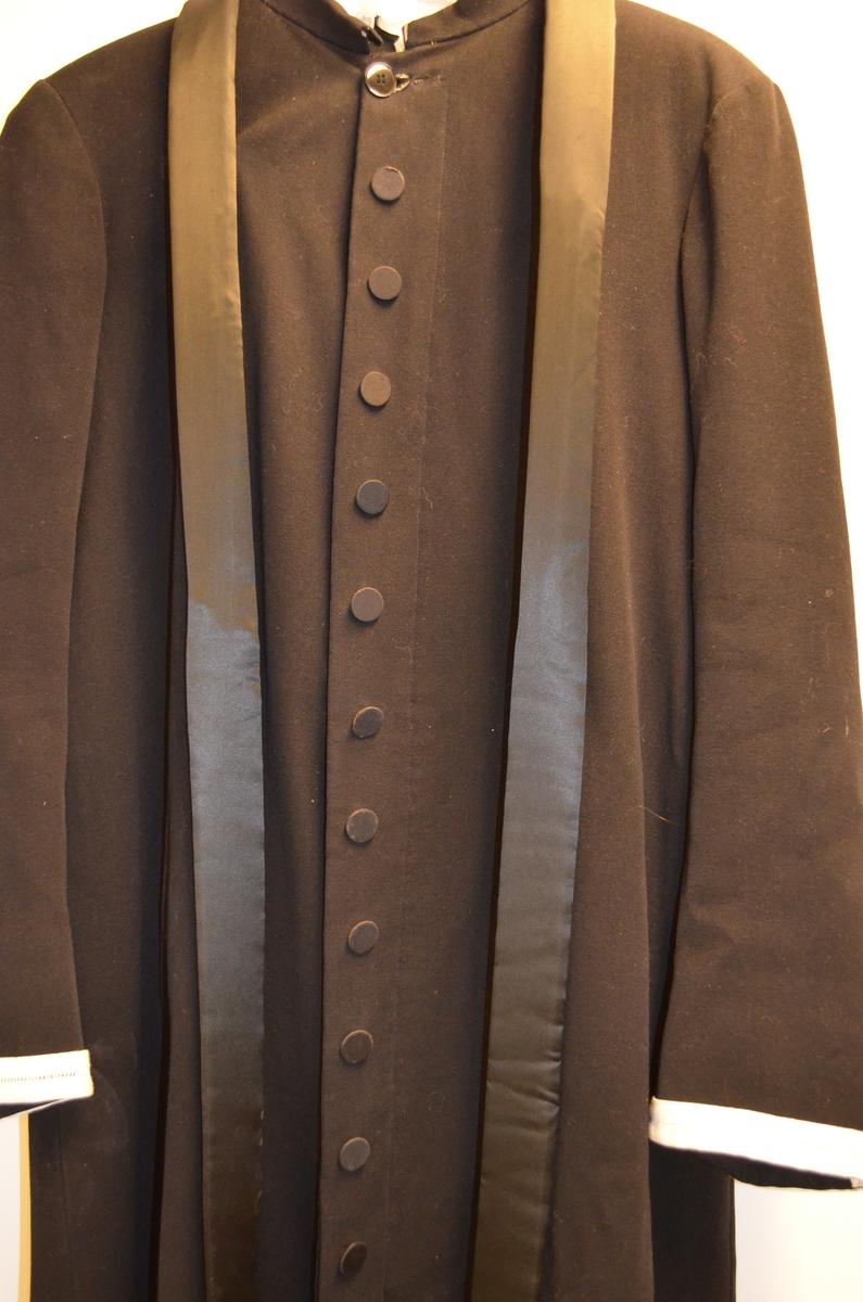 Prestekjole i svart klede med 21 knappar på den eine sida (pynt) og 8 på den andre, 8 knappehol. Avstiva krage i svart silke (?) som går heilt til nedrekanten av kjolen på båe sider. Midt bak 10 cm rynka pipefolder. Smal kant i kvit lin med holsaum framme på ermet. Fòra med svart silkefor.