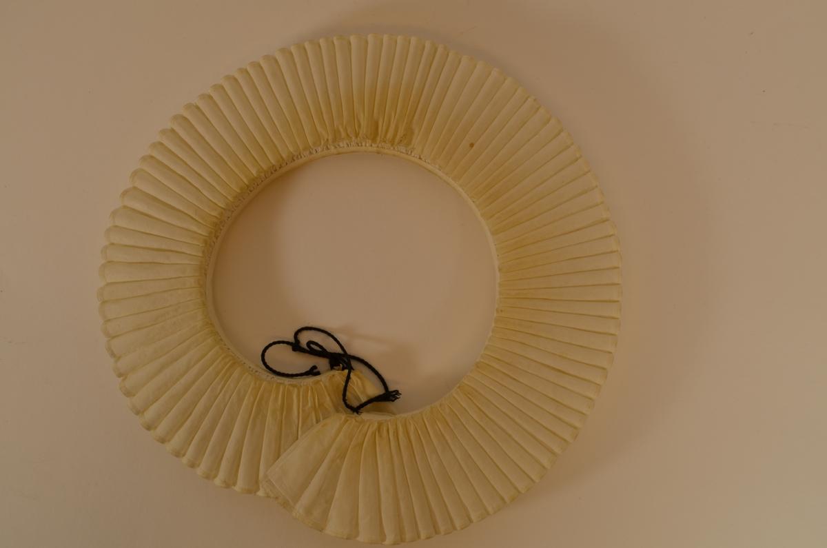 Pipekrage i stiva bomullstøy, sydd saman med tre lag tøy. To sydde hemper i knappeholsting i kvar ende for å feste band til å halde kragen saman med.