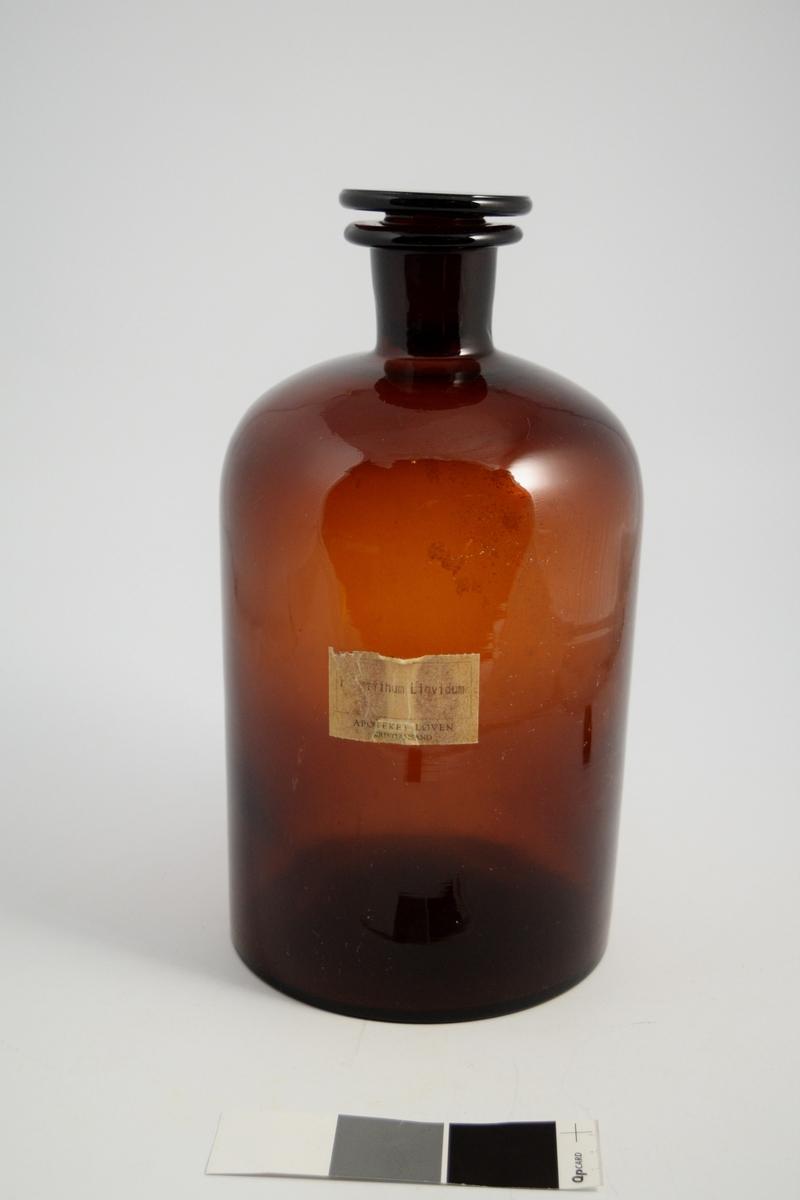 Brun glasskrukke med glasspropp. Maskinskrevet pålimt etikett. flytende parafin ble brukt i produksjon av salver og diverse flytende. Ble også brukt og solgt som avføringsmiddel.