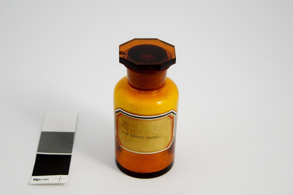 Brun glasskrukke med glasspropp. Påklistret hvit etikett med rød kant, skrevet med maskin. Inneholder krystaller av salisylsyre. Salisylsyre ble brukt i kremer og oppløsninger utvortes mot hudplager f.eks. eksem.