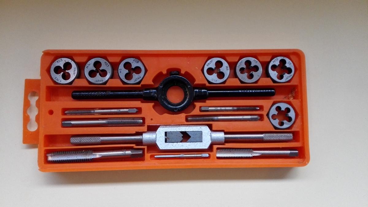 """Gjengesett med sju gjengetappar og sju gjengebakkar med ulik diameter, og holdarar både for tappar og bakkar. Verktøyet vert brukt til å laga både """"han""""- og """"ho""""-gjenger. Gjengesettet ligg i ein oransje plastboks med gjennomsiktig lok som kan skyvast av. Boksen kan hengast opp."""