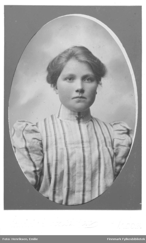 Portrett av ukjent kvinne. Hun er kledd i en stripete bluse med store puffermer og høy hals,  lukket med en tamp som minner om kinesisk lukning.