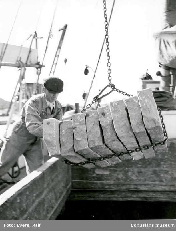 Lastning av kantsten med kran, en man skjuter på