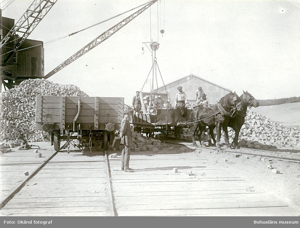 Lastning av gatsten på en vagn dragen av hästar längs en räls