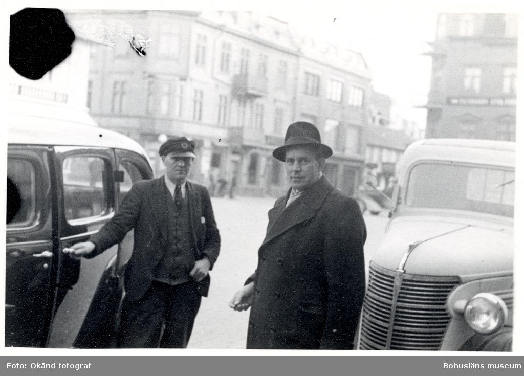 Två män står invid två bilar och blickar in i kameran