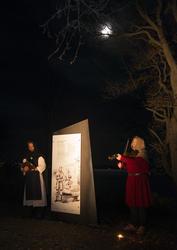 Munk i hvitt og svart synger mens mann i rød middelalderjakke og struthette spiller fiolin. Over lyser månen fra den mørke høsthimmelen.