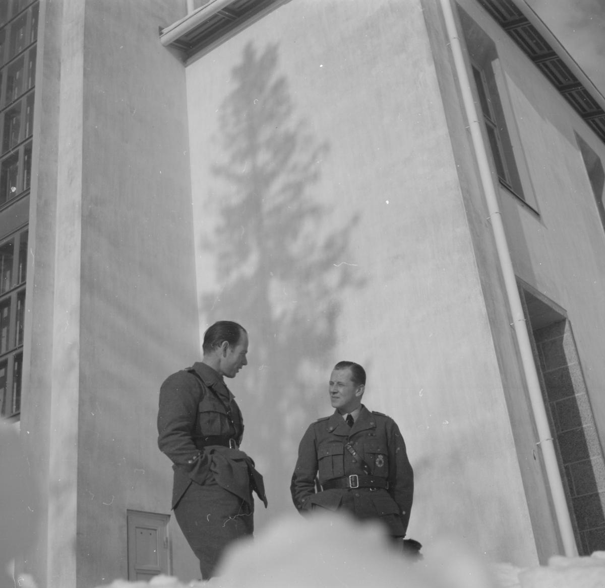 Två militärer tillhörande Svenska frivilligkåren i Finland, F 19, samtalar vid en byggnad. Snödriva i förgrunden.