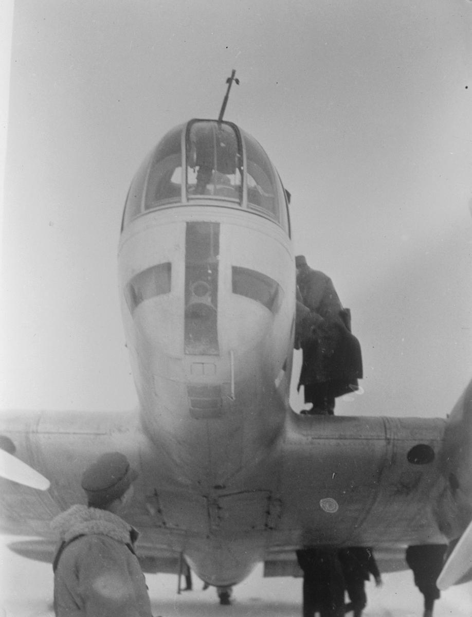 Närbild av nos av sovjetiskt flygplan Iljushin DB-3 på ett fält under finska vinterkriget, 1940. Människor i rörelse runtomkring. Bild från F 19, Svenska frivilligkåren i Finland.