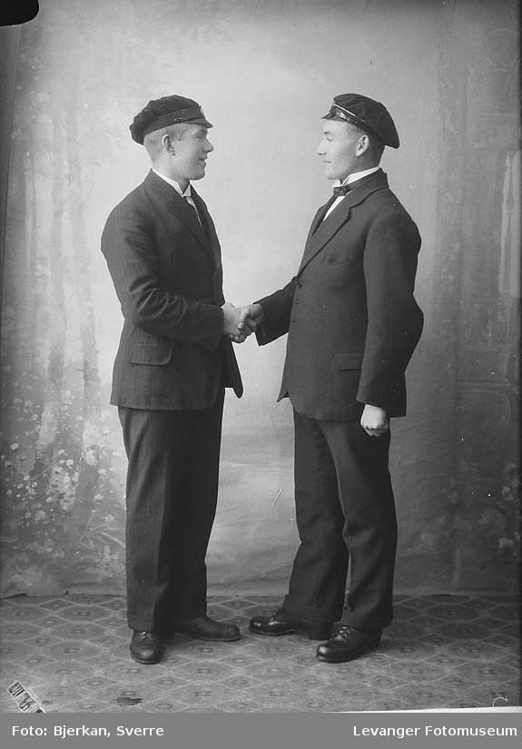 Portrett av to menn  som gratulerer hverandre med studenten  merket J. Selnes.