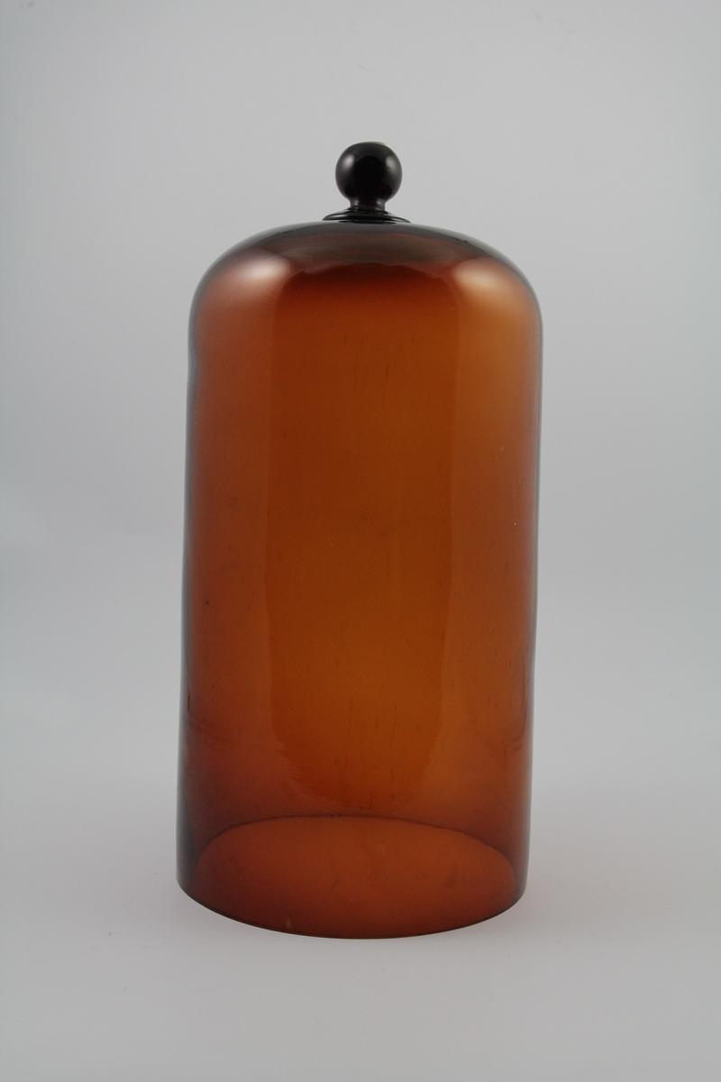 Brun glassklokke, rund kule på toppen som håndtak. Brukt til å sette over krukker, flasker eller lignende som inneholdt stoffer som er flyktige og avgir ubehagelig lukt.