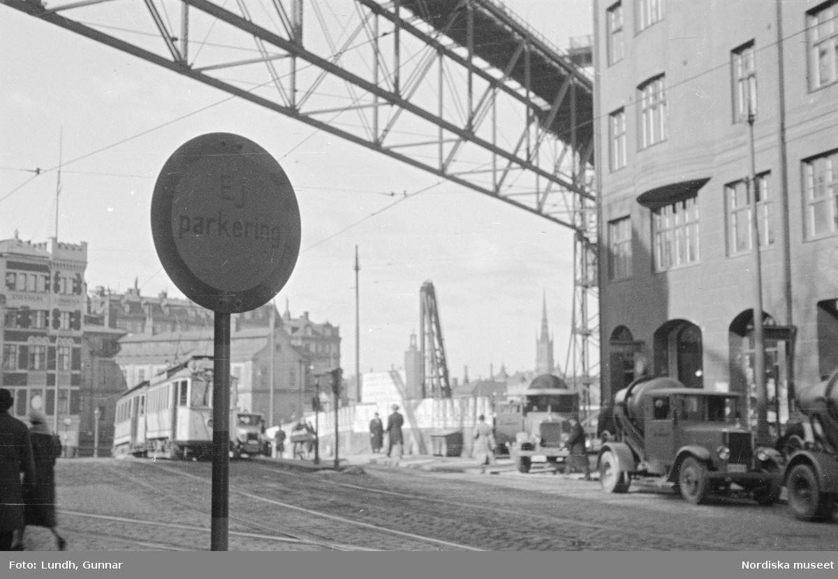 """Katarinavägen / Slussenområdet, Södermalm, Stockholm. I förgrunden en trafikskylt med texten """"Ej parkering"""". Fotgängare, spårvagn, lastbilar med cementblandare, Katarinahissen."""
