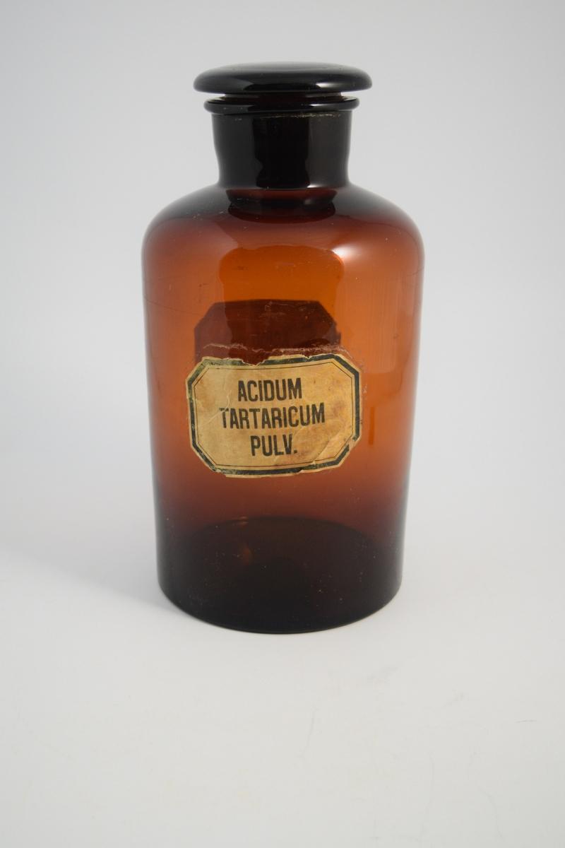 Brun glasskrukke med glasspropp. Påklistret hvit etikett med sort skrift. Slike krukker ble brukt til oppbevaring av pulver.