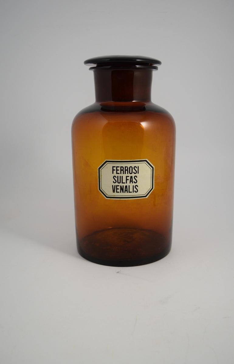 Brun glasskrukke med vid hals, brun glass propp. Påført hvit etikett med sort skrift. Krukken ble brukt til oppbevaring av pulver. Ferrosi sulfas venalis betyr jernsulfat, ikke rent. Dette innholdet ble brukt i veterinærmedisin.