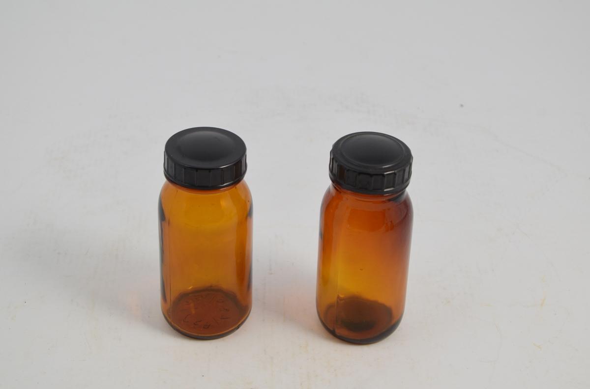 Apotekerflaske m/skrukork. Brune runde glasskrukker med sort bakelitt lokk. Glassene ble brukt til oppbevaring og slag av tabletter.