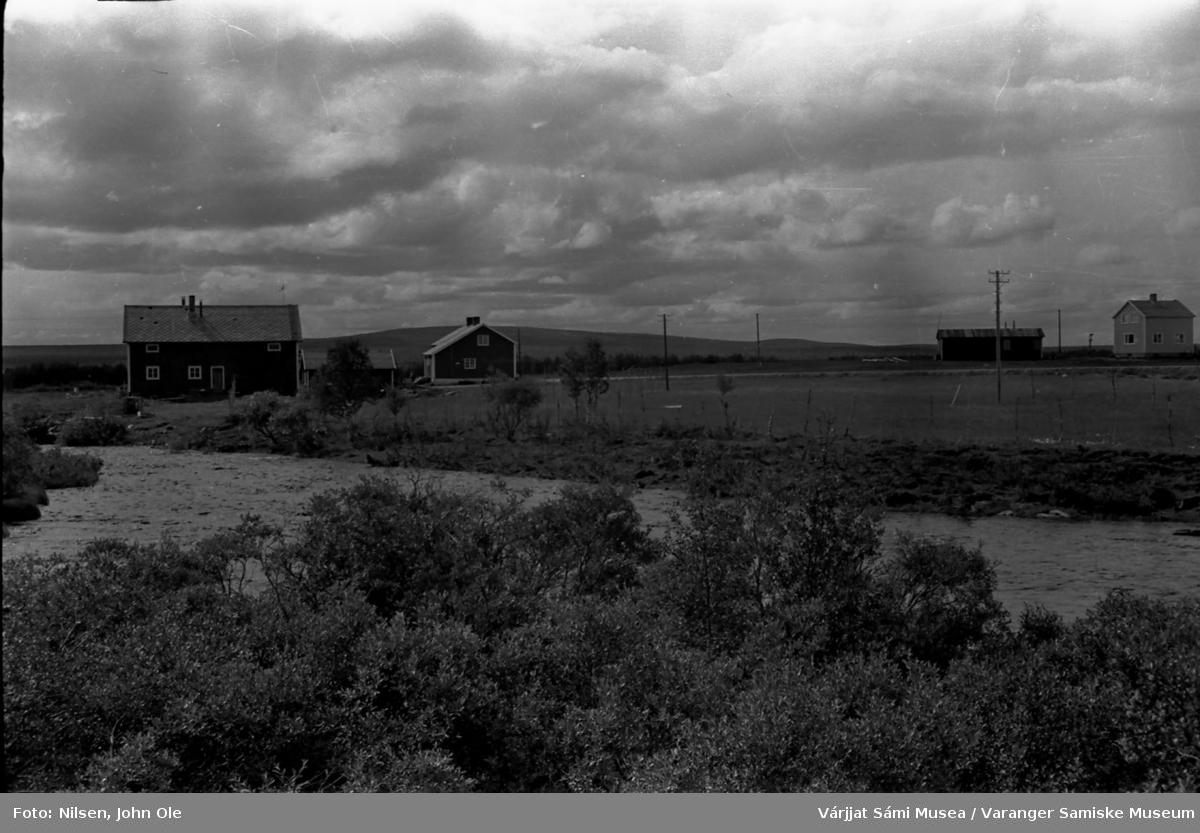 To bolighus med tilhørende bygninger, elv i forgrunnen. Ukjent sted, muligens i nærheten av Kautokeino. Juli 1967.