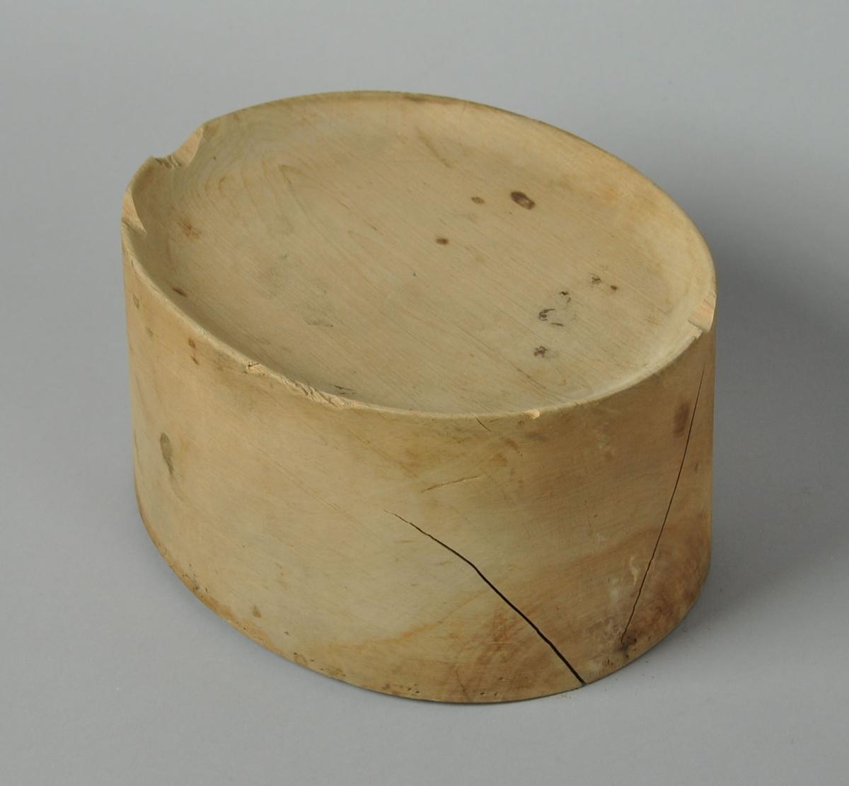 Oval hatteblokk med innfelt topp. Hatteblokken er satt sammen av to trestykker med spiker. På undersiden er det ett hull for skruefeste.