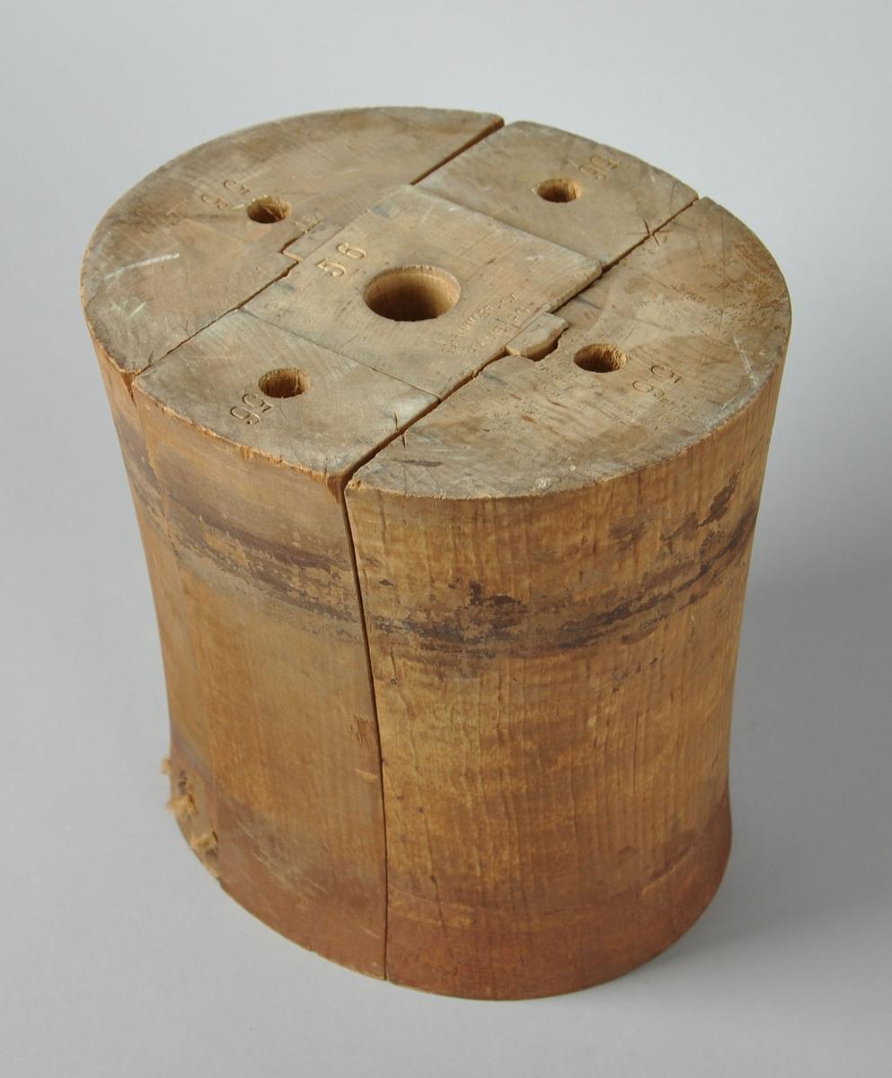 Sylinderformet hatteblokk hvor midtpartiet er innsnevret. Består av fem deler som står samlet. På undersiden av formen er det hull for skruefeste på alle delene.