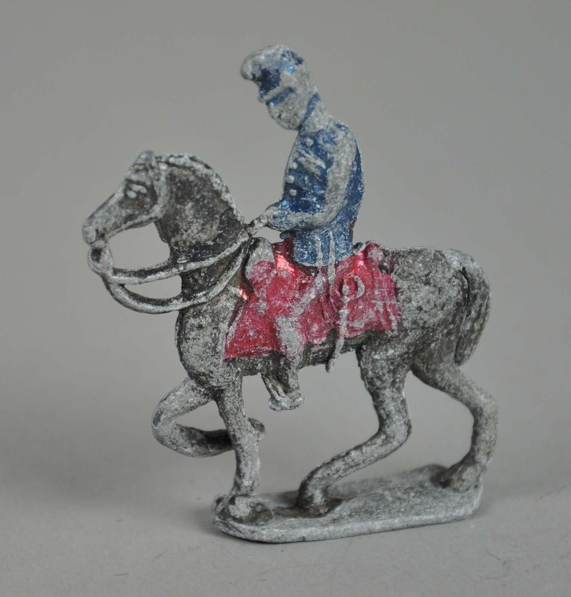 Liten figur av tinn. Figuren forestiller person på hest og står på en oval støtte. Spor etter maling på figuren.