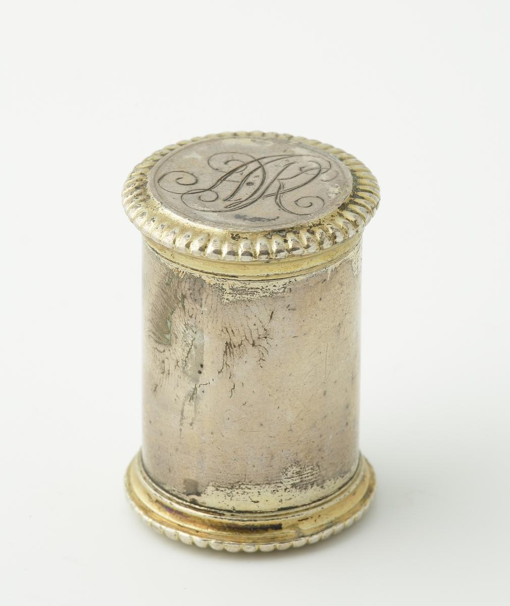 """Svampdosa med giftgömma (?), av silver. Cylindrisk modell bestående av två delar. I ena änden en svampdosa och i den andra en mindre giftgömma (?).  Dosan har räfflad dekor längs över- och nederkant. Delvis förgylld utsida. På locket graverat spegelmonogram: """"A.V.K."""" (?). I botten initialer: """"M.W., N.D."""". Invändigt förgylld. Saknar stämplar."""