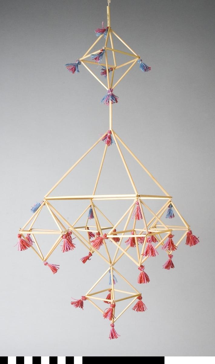 Halmkrona, handgjord. Modell med en större mittkvadrat, från vilkens hörn mindre kvadrater hänger. Dessutom en mindre kvadrat mellan takkrok och den stora kvadraten. I varje hörn sitter en tofs av ull- och bomullsgarn i blått, rött och rosa. Kronan är trädd med lintråd.