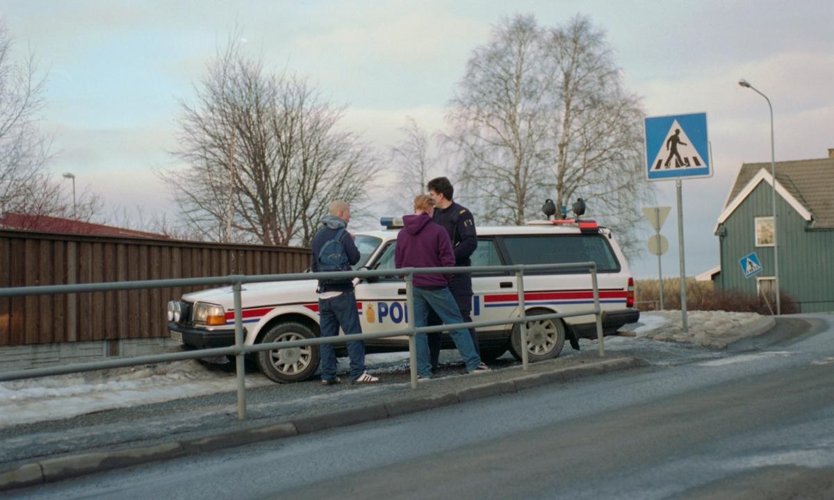To tenåringer og en politimann ved politibil på siden av veien.