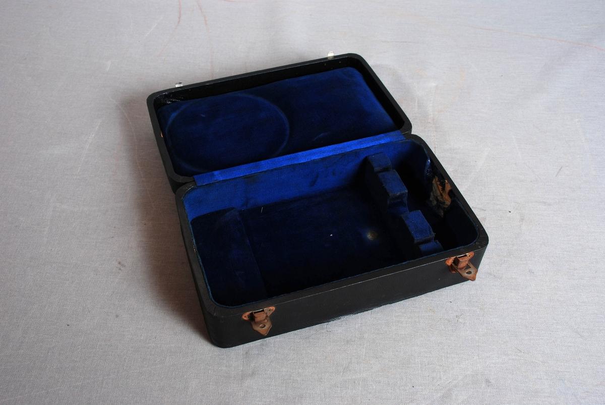 Rundt manometer med hals, festeskruer og metallskive . Manometeret ligger i rektangulært etui med lukking fremme. Etuiet er foret med tekstil, i lokket er det vatt under foret.