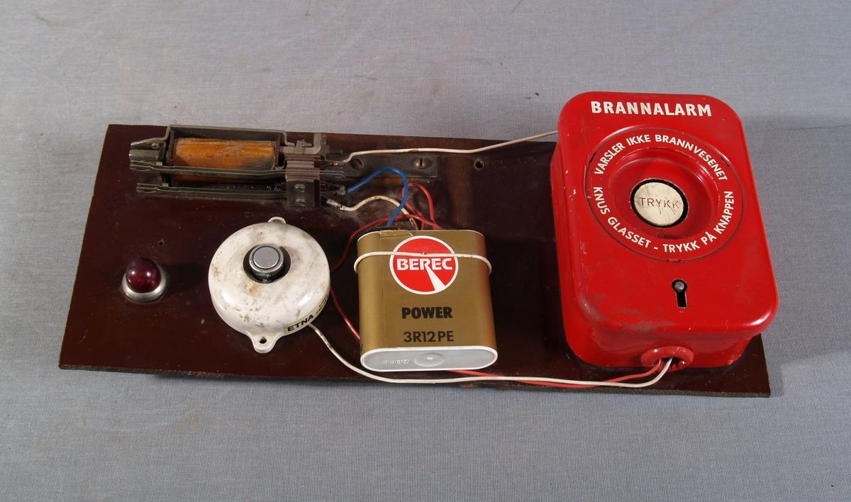 Manuell melder og varmemelder festet på tavle av bakelitt. De er koplet til 4,5-volts batteri, en spole og en rød varsellampe.