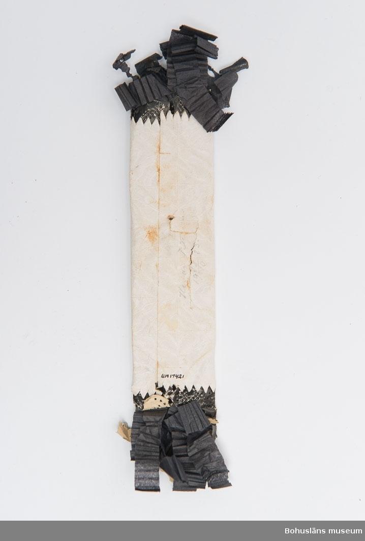 Vitt omslag med påklistrad försilvrad kalk med kors med svart pappersspets ock klippta veckade svarta fransar.  Ytterligare kring förvärvet se Information Intern.