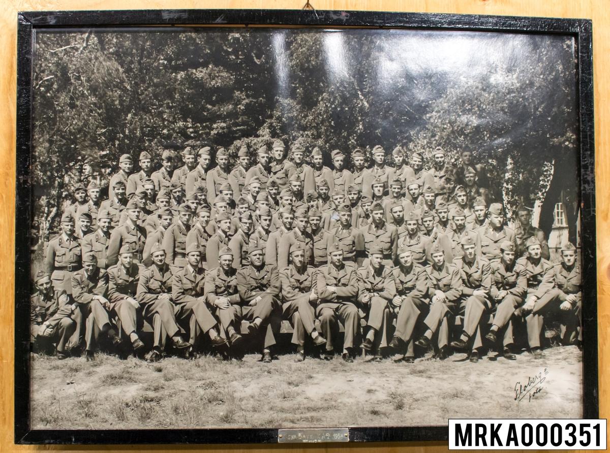 Fotografi taget på befäl och soldater som genomfört grundläggande soldatutbildning på 1:a Batteriet KA 2. Fotografiet taget på KA 2. Flobergs Foto 1958.