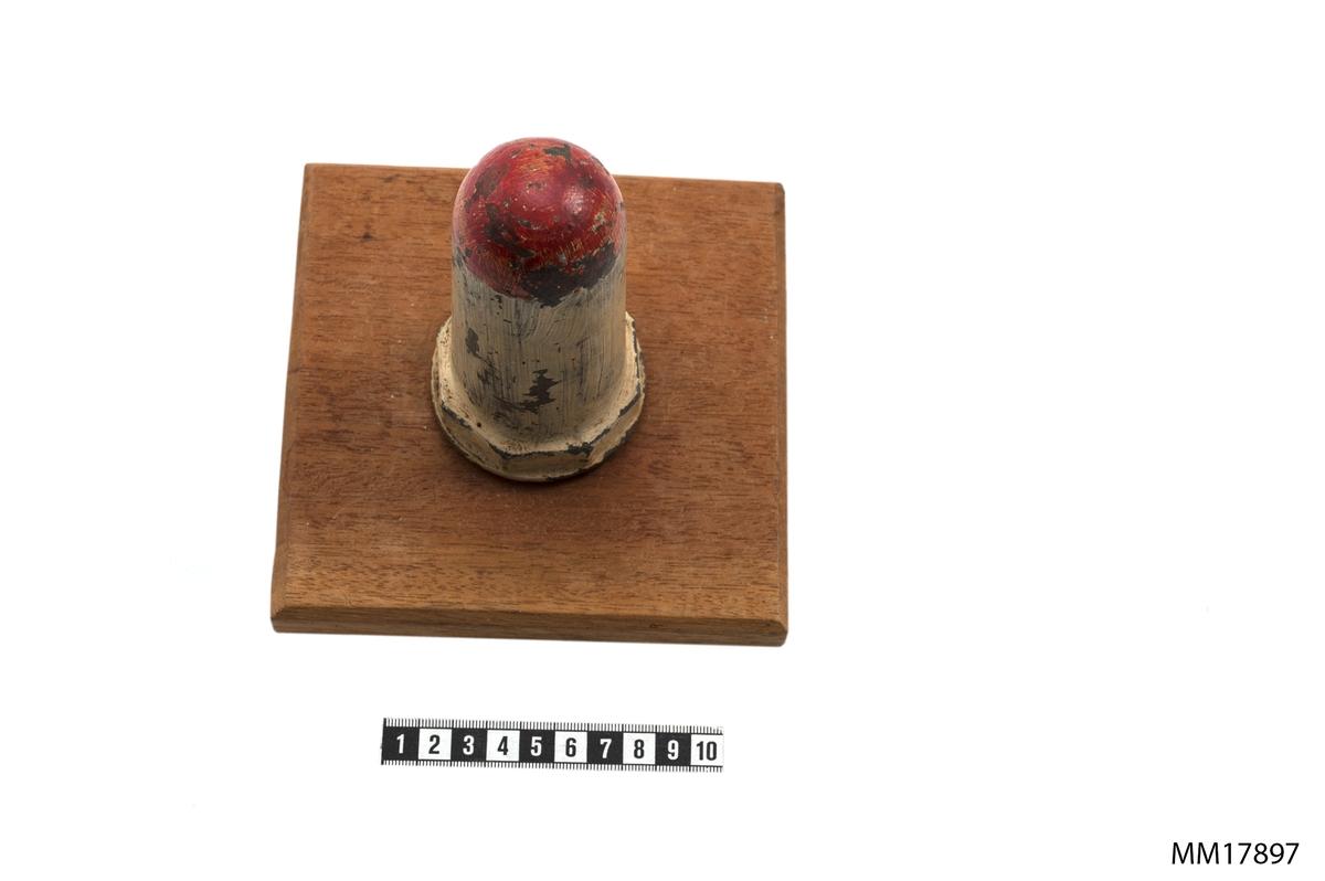 Minhorn av järn, gulmålat med röd spets. Fästad till kvadratisk platta av teak genom en träplugg som är fastskruvad i plattans mitt och som minhornet sitter på.