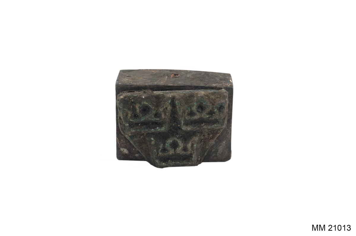 """Trähandtag i form av en knopp. Ena sidan är avfilad, där syns ett """"E4"""" tryckt i svart. Foten är rektangulär med tre kronor i metall under."""