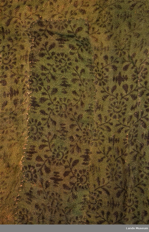 4 skinnknapper med skinnhemper. Foret: grønt stoff med trykk mønster: sort blomstermotiv. Ermene foret mer beige stoff. Krave i glatt skinn.