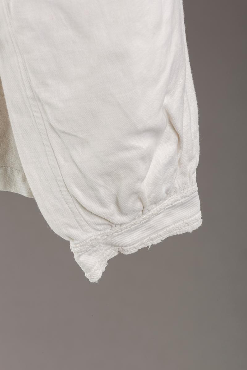 Form: Hoftelang trøye, Lange ermer, krage. Kragen og åpningen foran er kantet med  maskinprodusert blonde. Tre biser på hver side av åpn. foran. Lukkes med to løse knapper.