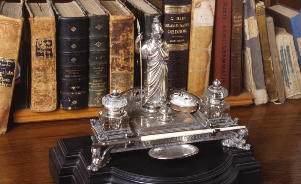 Sokkel, understell, to blekkhus og løsjer. Blekkhusene er i slepet krystall og har brutte hjørner, lokkfeste i sølv og lokk i sølv og krystall.  Foran på oppsatsen står en romersk figur.
