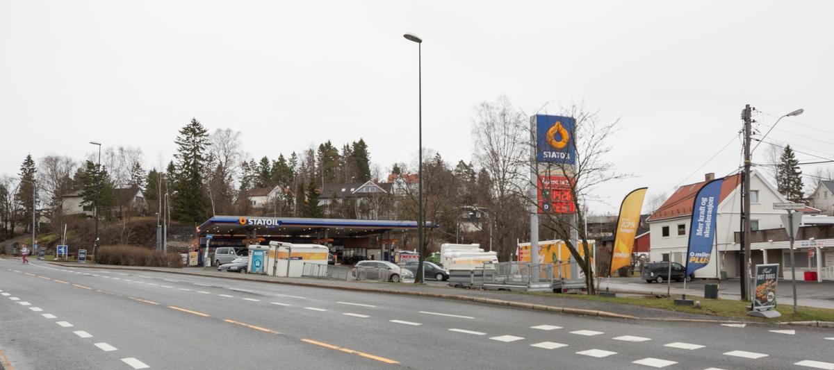 Statoil Nadderud. Bensinstasjon sett fra veien. Veiskilt Statoil i forgrunnen. Reklamebannere og utleietilhengere.