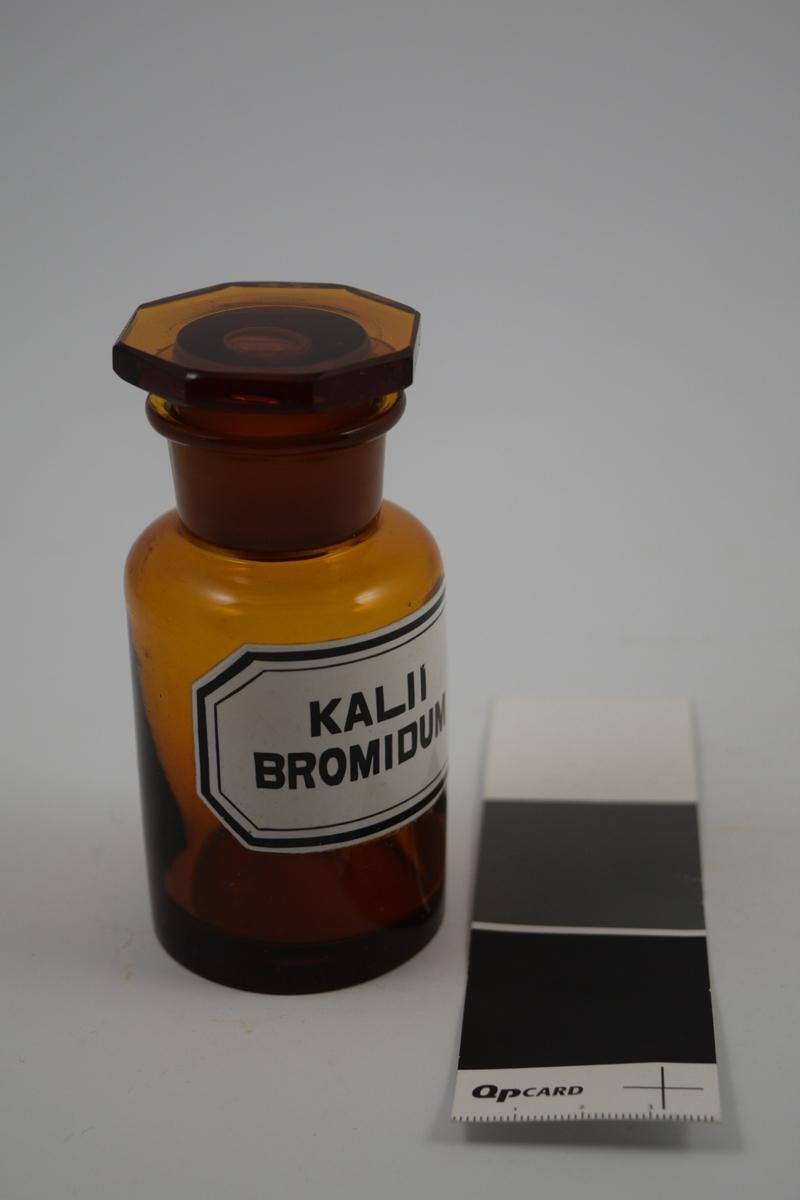Brun glasskrukke med åttekantet glasspropp. Hvit etikett med sort skrift. Krukken ble brukt til oppbevaring av Kalii bromidum, som ble brukt som sovemiddel.