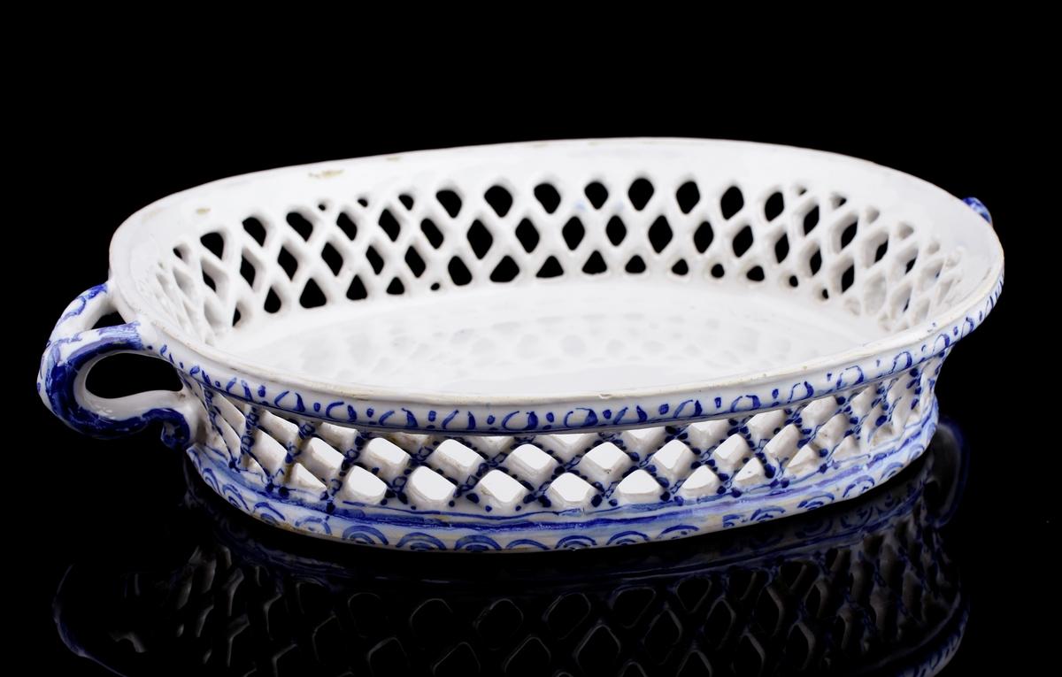 Gallerskål i fajans. Oval modell med handtag. Blå handmålad dekor i form av små rundlar och halvcirklar.