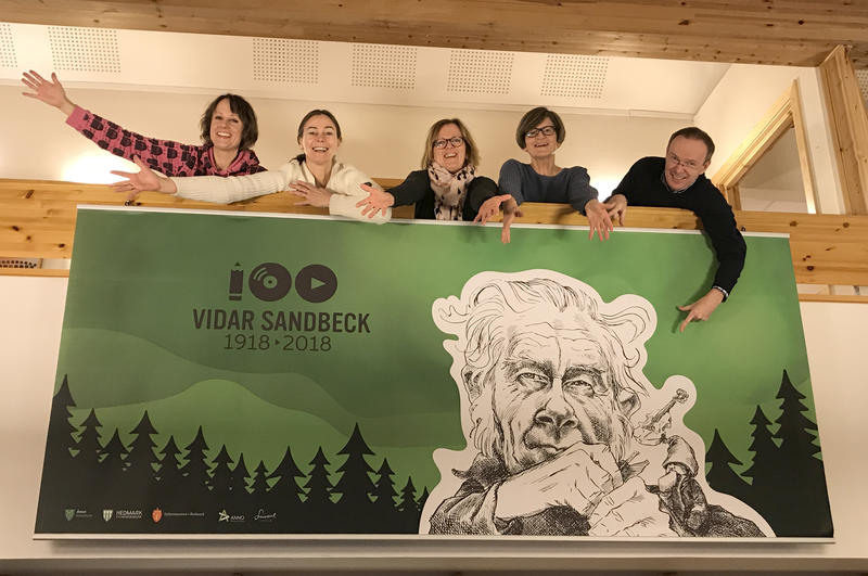 Ansatte ved Kulturkontoret i Åmot kommune bak banner med Vidar Sandbeck-jubileet.