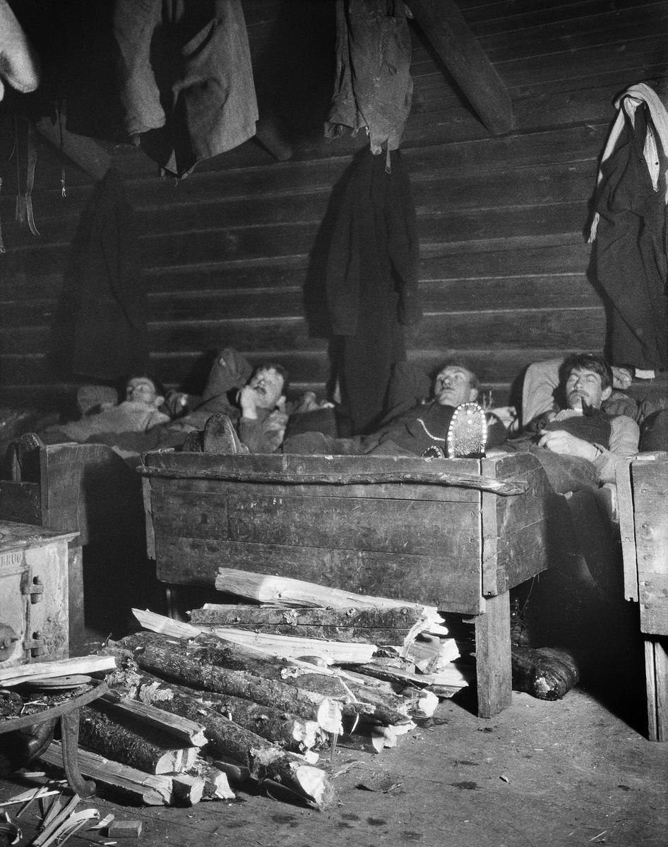 Uke 3: En velfortjent hvil i koia! Ukas bilde viser et fotografi som er tatt i forbindelse med Johan Sønnik Andersens undersøkelse av skogshytter og skogarbeidernes levevilkår. Bildet er tatt i 1931.