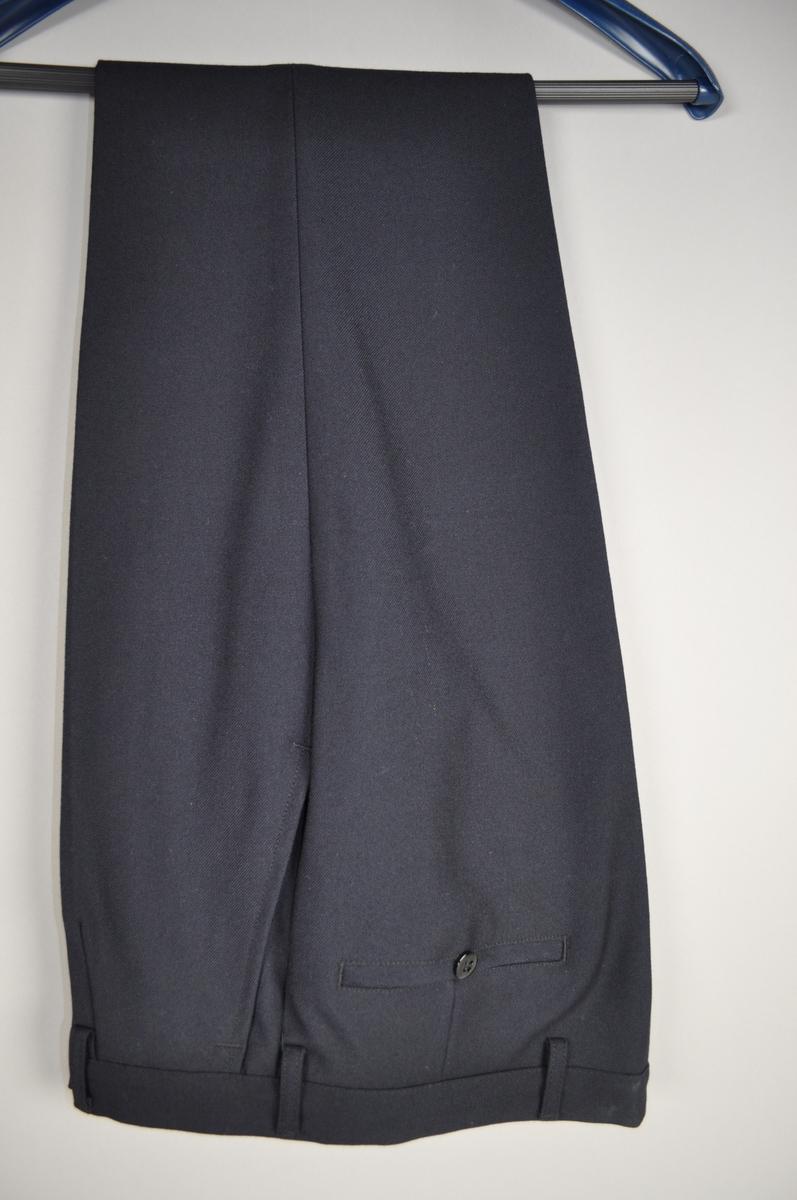 Postuniform bestående av jakke og bukse med posthorn med ekeløv og 3 stjerner. Gullfargede uniformsknapper med posthorn.